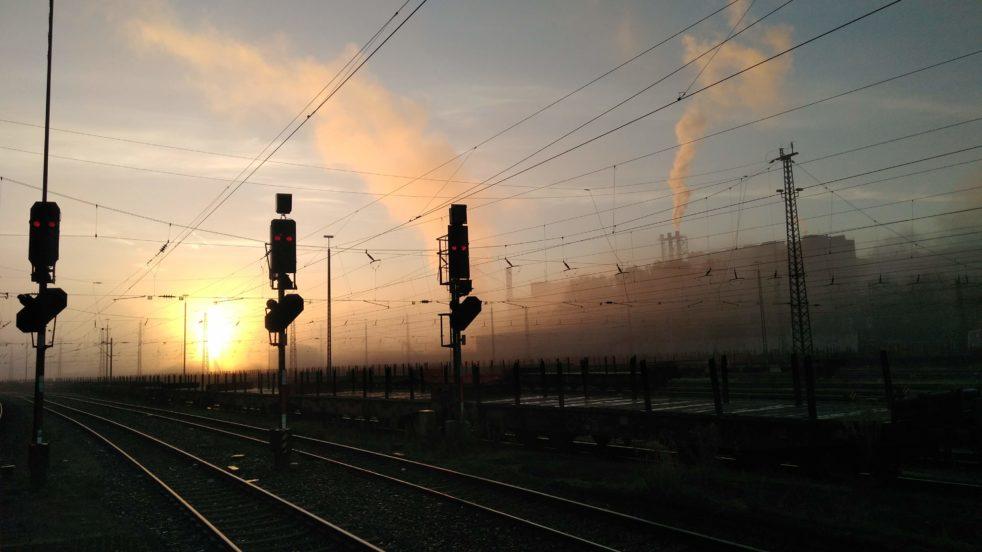 Ampelanlagen und Gleisbett bei Sonnenaufgang am Bahnhof in Völklingen.