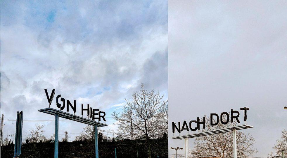 """In großen Lettern steht am Busbahnhof """"von hier nach dort"""". Ein Kunstwerk von Ralf Werner."""