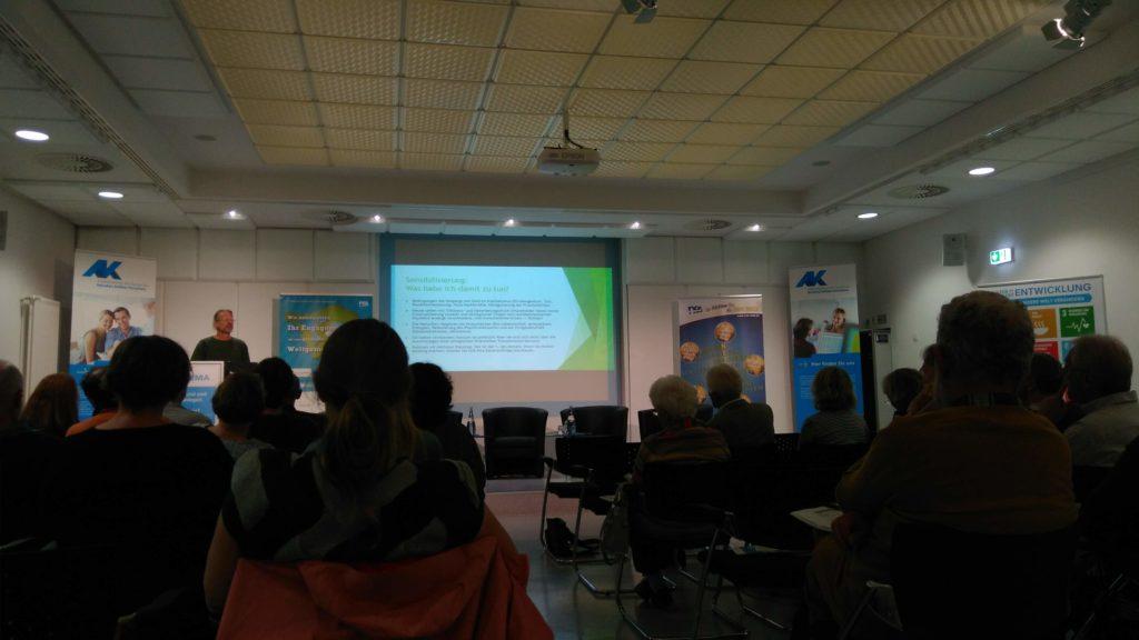 """Ekkehart Schmitt hält auf einer Veranstaltung der Arbeitskammer des Saarlandes einen Vortrag zum Thema """"Geld als Hebel für Veränderung""""."""